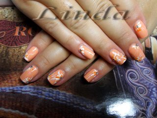 Декоративен маникюр - рисунки на цветя с оранжева и бяла боичка, украсени в средата с цветни камъчета